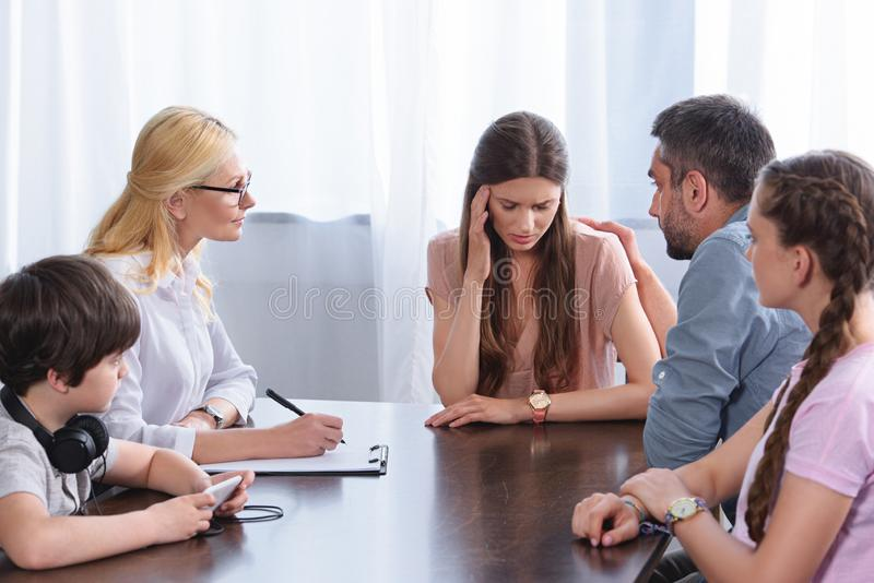Female counselor writing in clipboard while family cheering up woman. Female counselor writing in clipboard while family cheering up women in office on therapy stock image