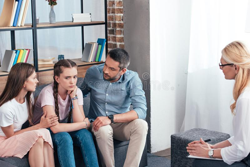 Female counselor writing in clipboard while parents cheering up daughter. On therapy session stock images