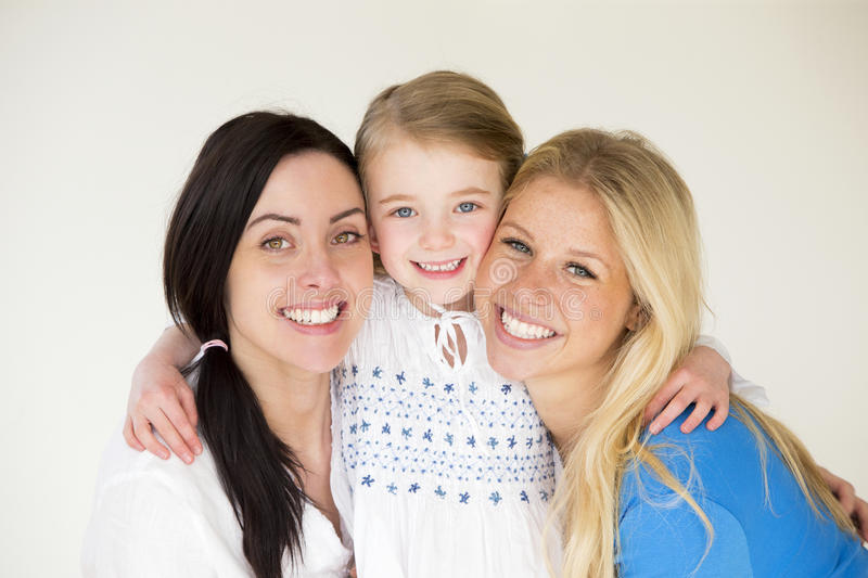 Female couple with daughter. Same sex female couple posing with their daughter in front of a plain background royalty free stock images