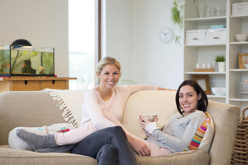 Female couple having tea at home. Same sex female couple smile together for the camera whilst relaxing in their home royalty free stock image