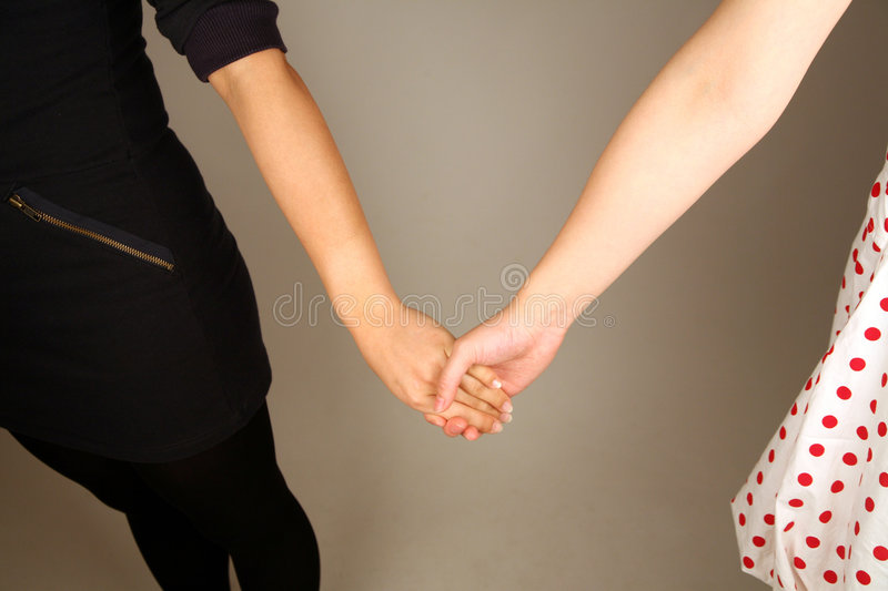Female couple holding hands. Lovingly and with care stock image