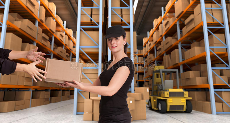 Female courier at warehouse b. Female courier carrying a parcel in a distribution warehouse royalty free stock photo