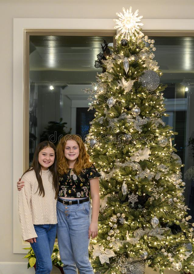 Female cousins posing by a Christmas tree on Thanksgiving in Edmond Oklahoma royalty free stock images