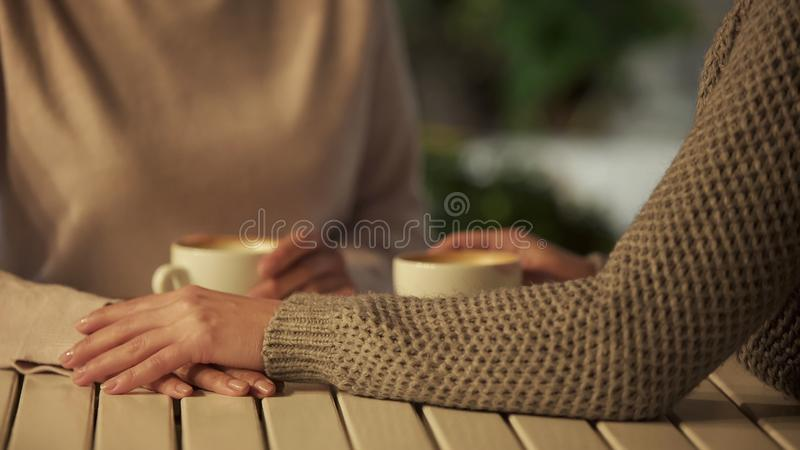 Female covering friend hands closeup, friendship support, close relations, trust. Stock photo stock images