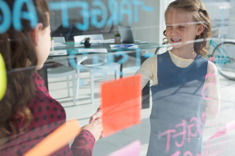 Female coworkers giving handshake at office seen through glass royalty free stock image