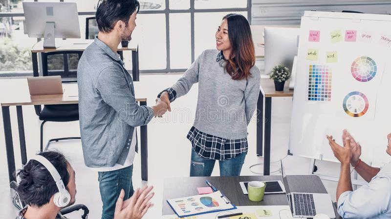 Female creative director boss handshake with designer and congratulation about getting promotion of job in modern creative office.  royalty free stock photos