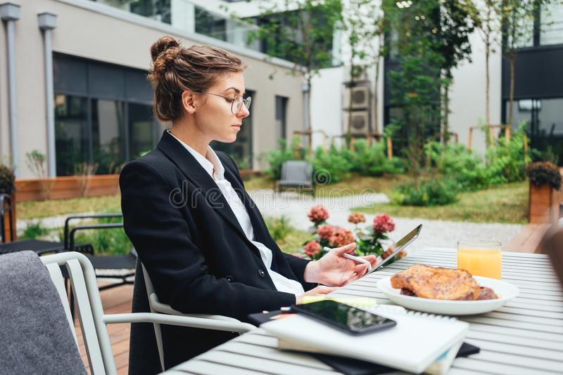 Business woman using digital tablet and pen while sitting at coffee shop stock images