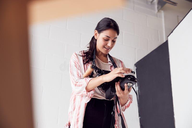 Female Crew Member On Video Film Set Operating Wireless Follow Focus Module In White Studio stock photo