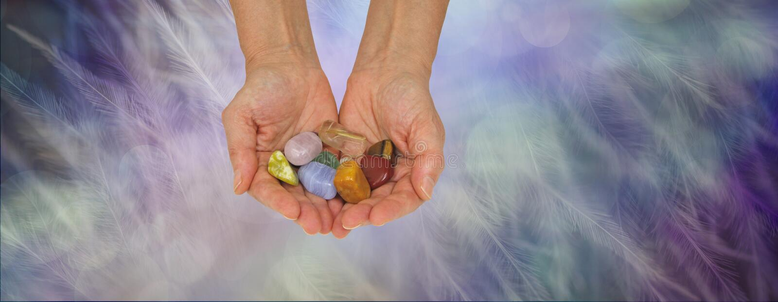 Crystal healing practitioner offering selection of tumbled healing stones stock image