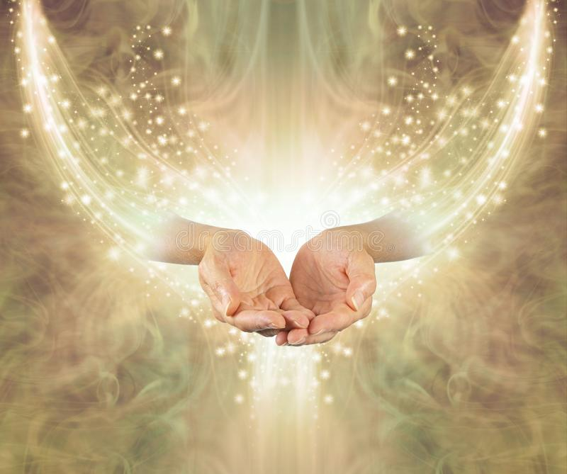 Golden Healing Resonance. Female cupped hands emerging from arc of shimmering sparkles on a glowing golden ethereal energy formation background with copy space royalty free stock photography