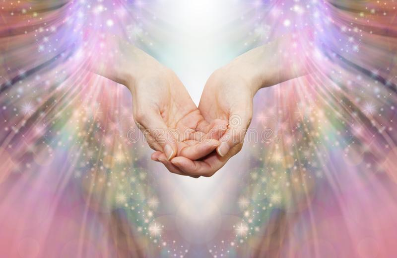 Energy healer receiving high vibrational energy. Female cupped hands and shaft of white light against an angelic pink and sparkle energy flow background royalty free stock images