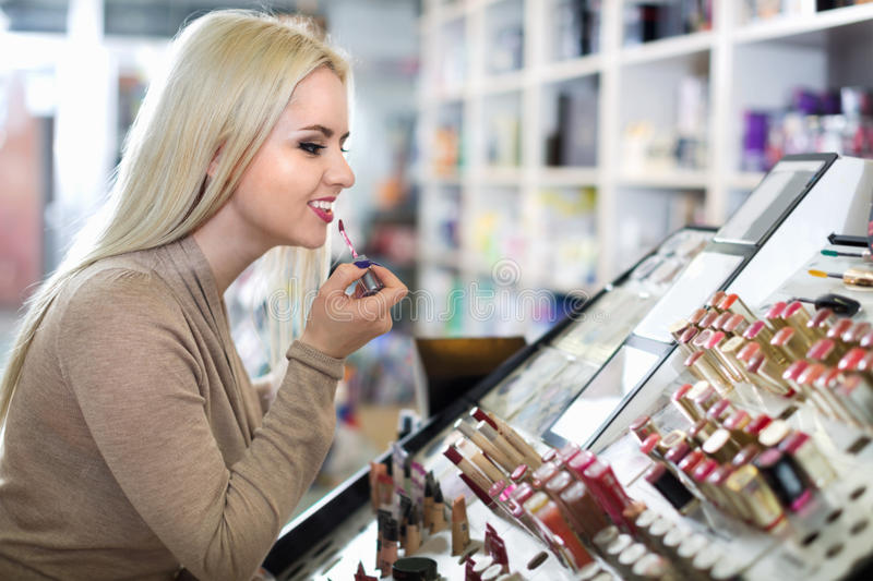 Female customer buying red lipstick in makeup section. Happy female customer buying red lipstick in makeup section royalty free stock image