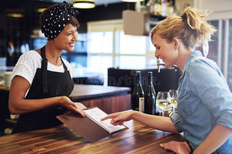 Female customer choosing wine in a bar. Female customer choosing wine from a wine list being presented to her by a charming young African American bartender in a royalty free stock images
