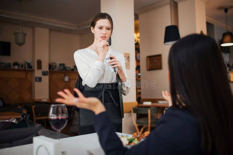 Female customer complain to waitress. She hold hands aside. Waitress look at her with concern. She stand at table where. Customer sit royalty free stock photos