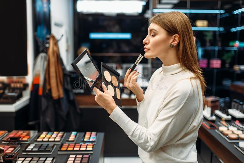 Female customer looks at the mirror in makeup shop. Female customer looks at the mirror in the makeup shop. Nail varnish choosing in beauty store, make-up salon royalty free stock photography