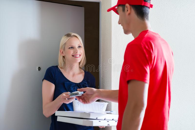 Female customer making payment to delivery man royalty free stock image