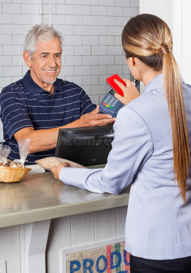 Download Female Customer Paying Through Mobile Phone In Stock Photo - Image: 37112656