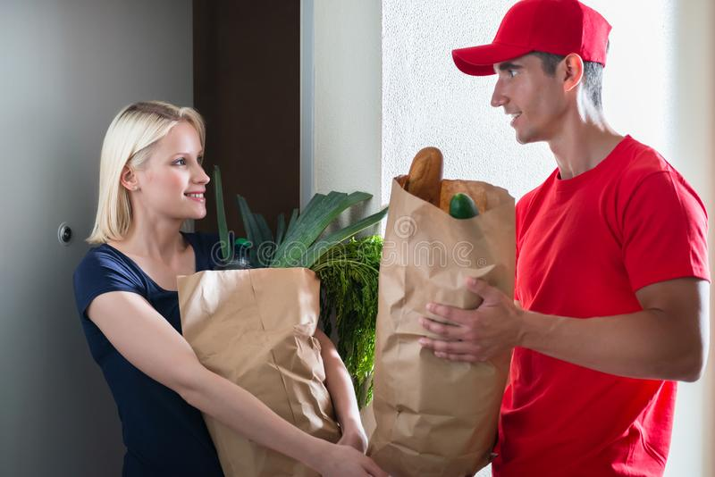 Female customer receiving the grocery delivery. Smiling young female customer receiving the grocery delivery from men in red uniform royalty free stock photos