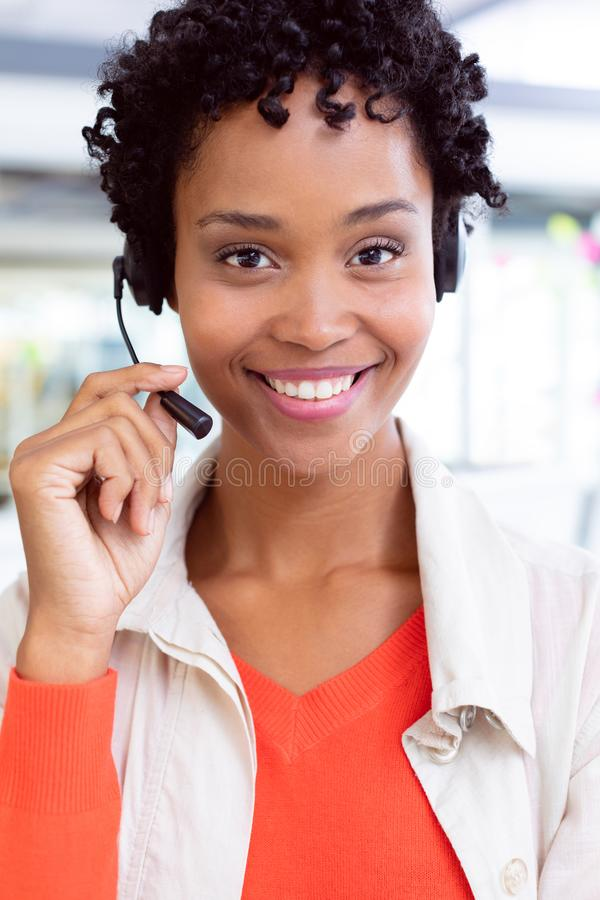 Female customer service executive with headset looking at camera in office stock photography