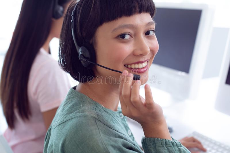 Female customer service executive working on computer at desk in office. Portrait of Asian female customer service executive working on computer at desk in stock photography