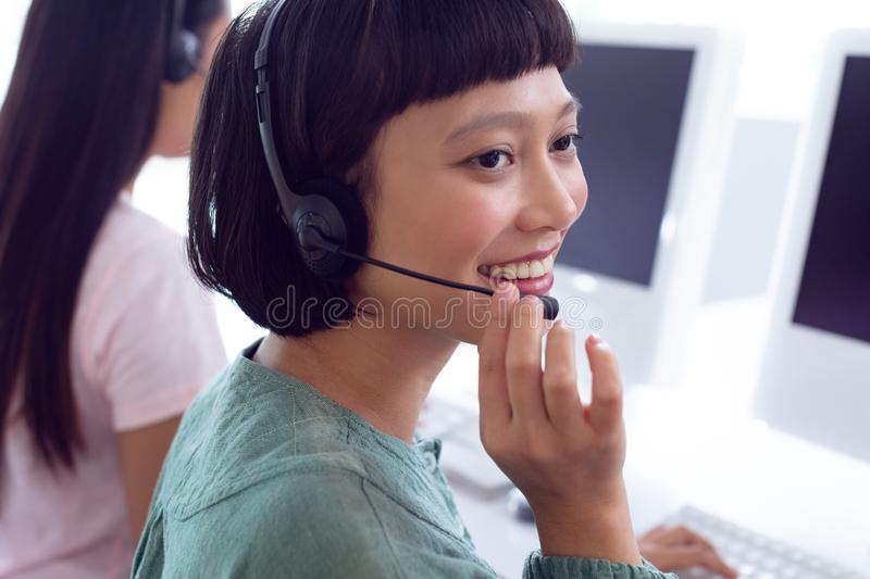 Female customer service executive working on computer at desk. Side view of Asian female customer service executive working on computer at desk in office royalty free stock images