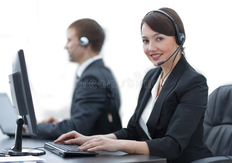 Female Customer Services Agent With Headset Working In A Call Center. Positive Female Customer Services Agent With Headset Working In A Call Center royalty free stock photo