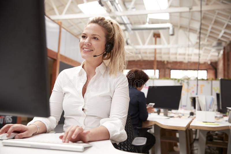 Female Customer Services Agent Working At Desk In Call Center royalty free stock photo