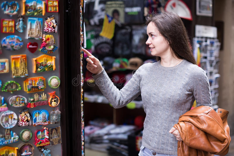 Female customer in souvenir shop. Positive young woman choosing things for memory in souvenir shop stock images