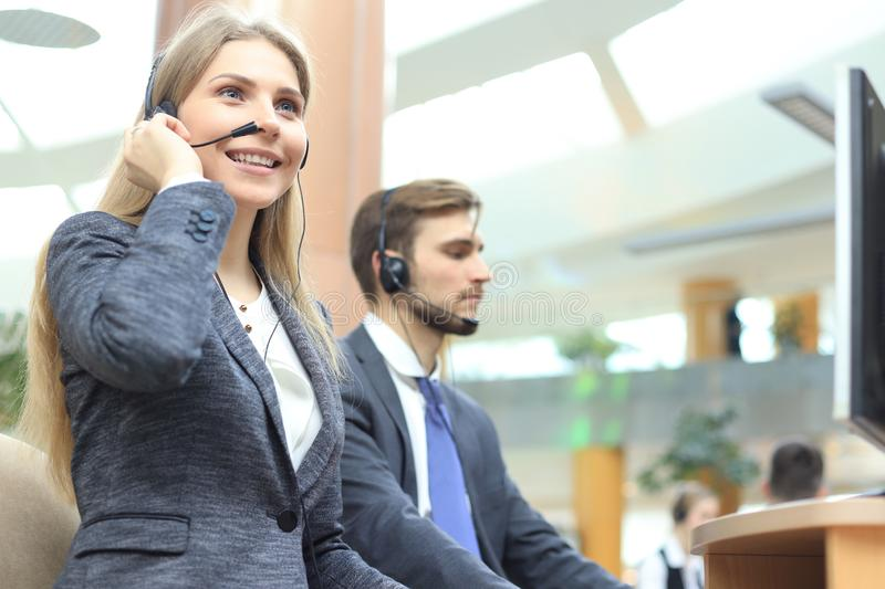 Female customer support operator with headset and smiling stock images