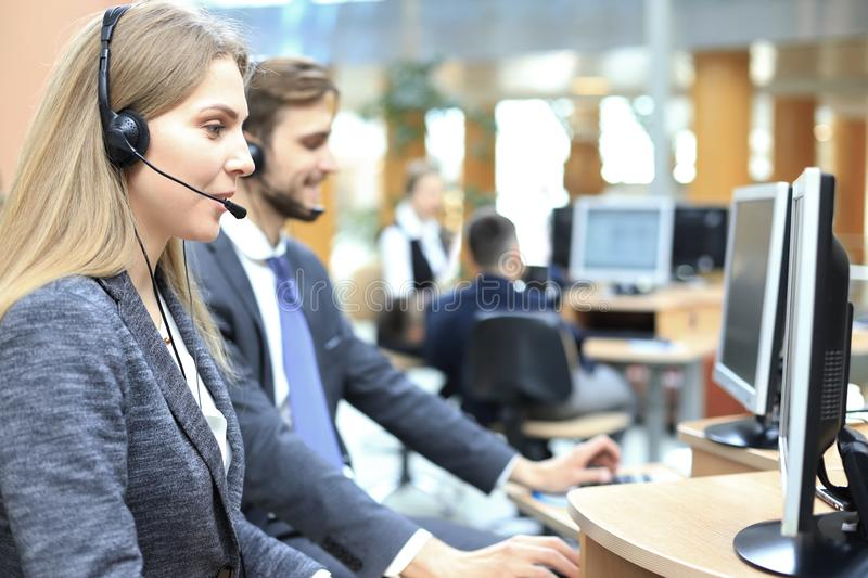 Female customer support operator with headset and smiling stock photography
