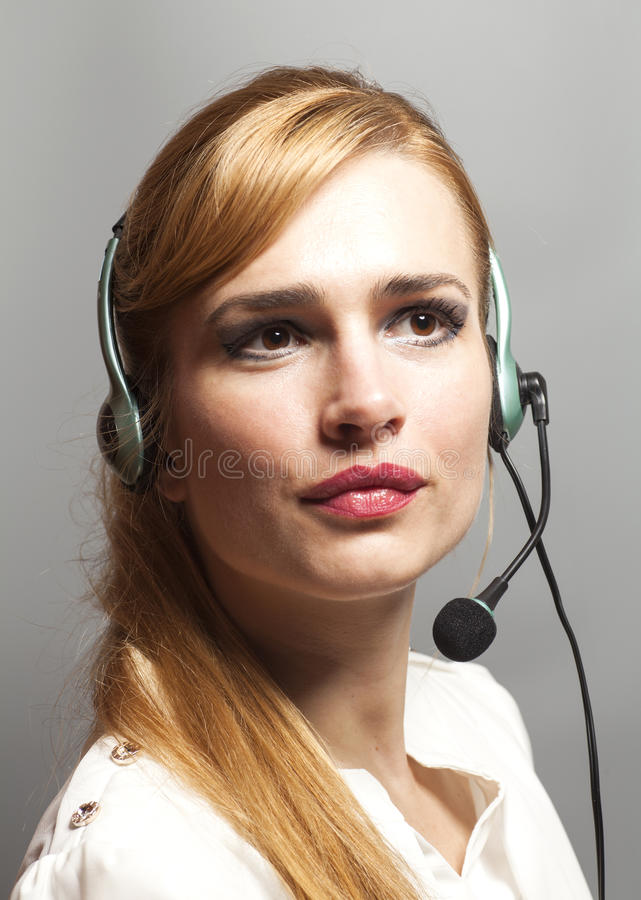 Female customer support operator with headset and smiling isolated on gray background royalty free stock photos
