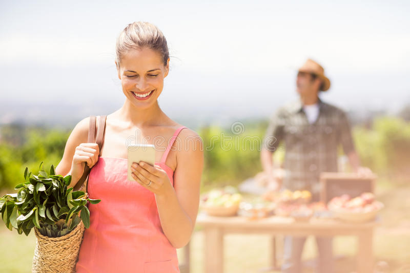 Female customer using mobile phone in front of vegetable stall. At local market royalty free stock photo