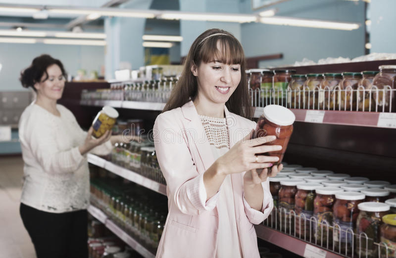Female customers looking at jars with pickles royalty free stock photo