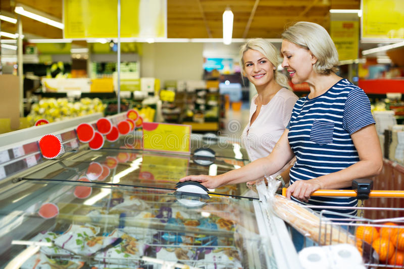 Female customers near display with frozen food stock images