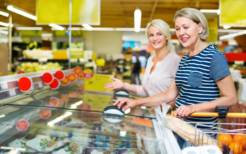 Female customers near display with frozen food stock photography