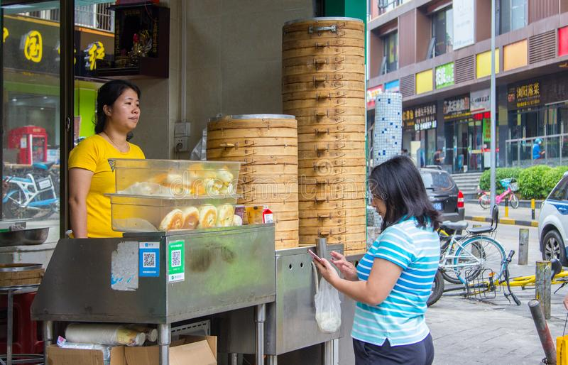 A female customers uses smartphone to pay her breakfast at a street booth with Qr code royalty free stock photos