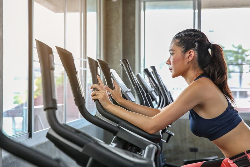 The female is cycling in the gym. Portrait of girl exercising on cardio machines in the sport club. Pretty women body builder royalty free stock images