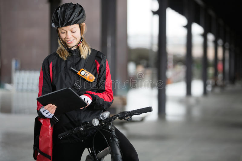 Female Cyclist With Courier Bag Using Digital royalty free stock photo