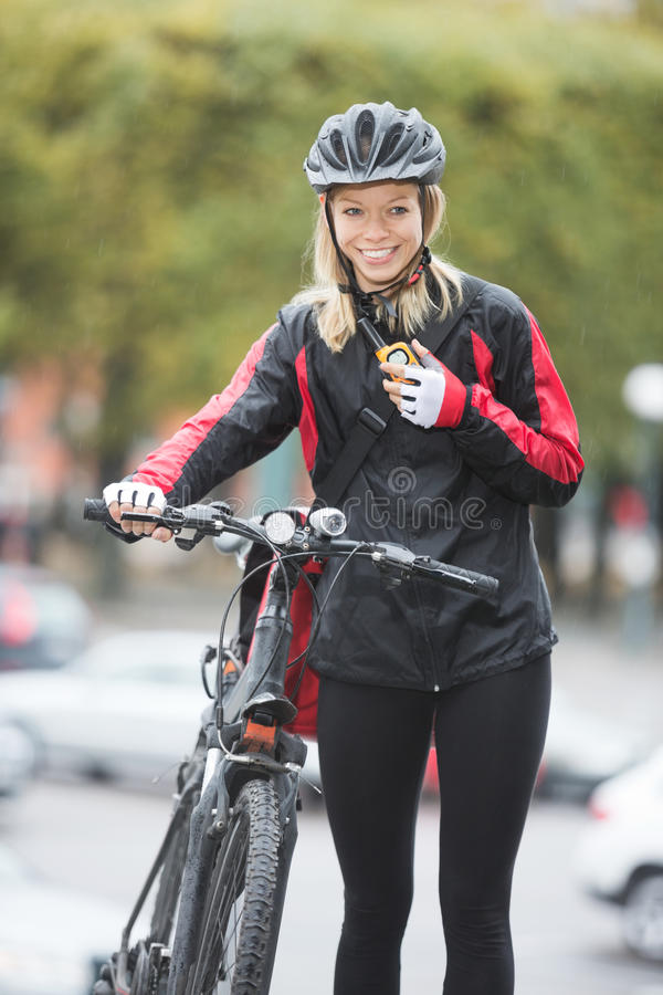 Female Cyclist With Courier Bag Using royalty free stock photos