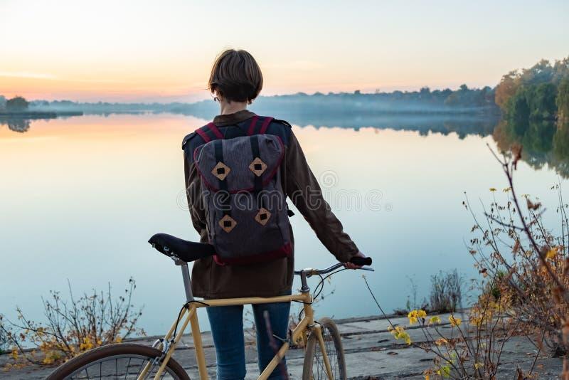 Female cyclist enjoying beautiful blue hour scene by the lake. W stock image