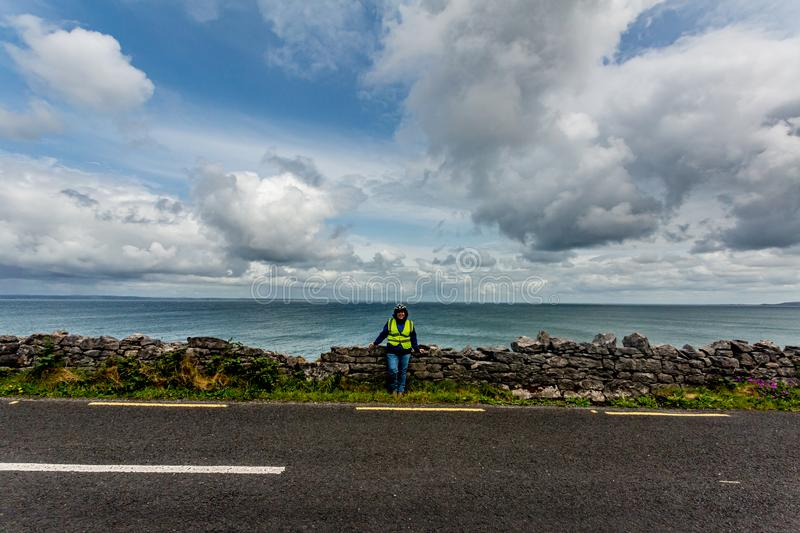 Female cyclist having a break on the coastal R477 road. Between Bothar nA hAillite and Fanore, geosite and geopark, Wild Atlantic Way, spring day in county royalty free stock photo