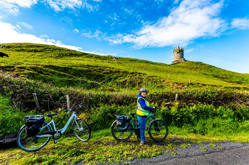 Female cyclist having a break with the Doonagore Castle tower in the background stock photography