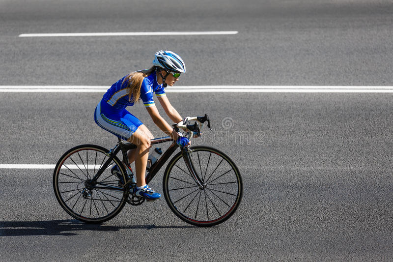 Female cyclist rides a racing bike on road royalty free stock photography