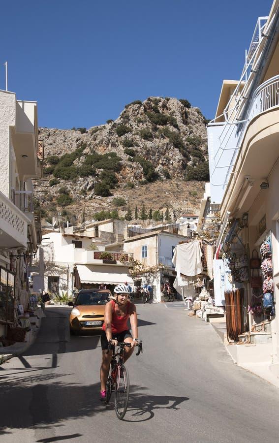 Female cyclist riding through a Cretan village royalty free stock photos
