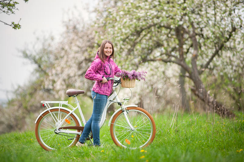 Female cyclist with vintage white bicycle in spring garden. Smiling brunette woman wearing purple jacket and jeans with a vintage white bicycle and lilac flowers royalty free stock photos