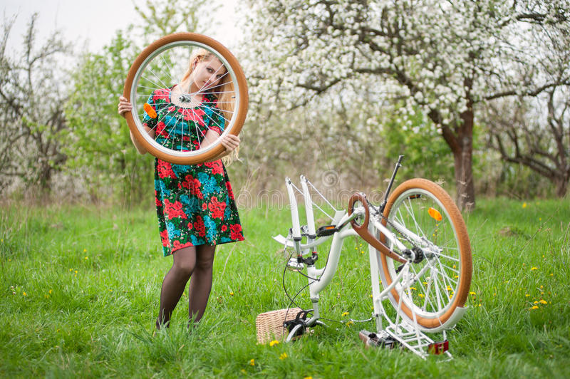 Female cyclist with vintage white bicycle in spring garden. Young woman with long blonde hair in flowered dress standing next to white retro bicycle upside down royalty free stock photo