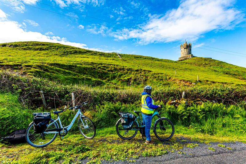 Female cyclist watching the Doonagore Castle tower in the coastal town of Doolin. Wild Atlantic Way, wonderful sunny day in County Clare in Ireland royalty free stock images