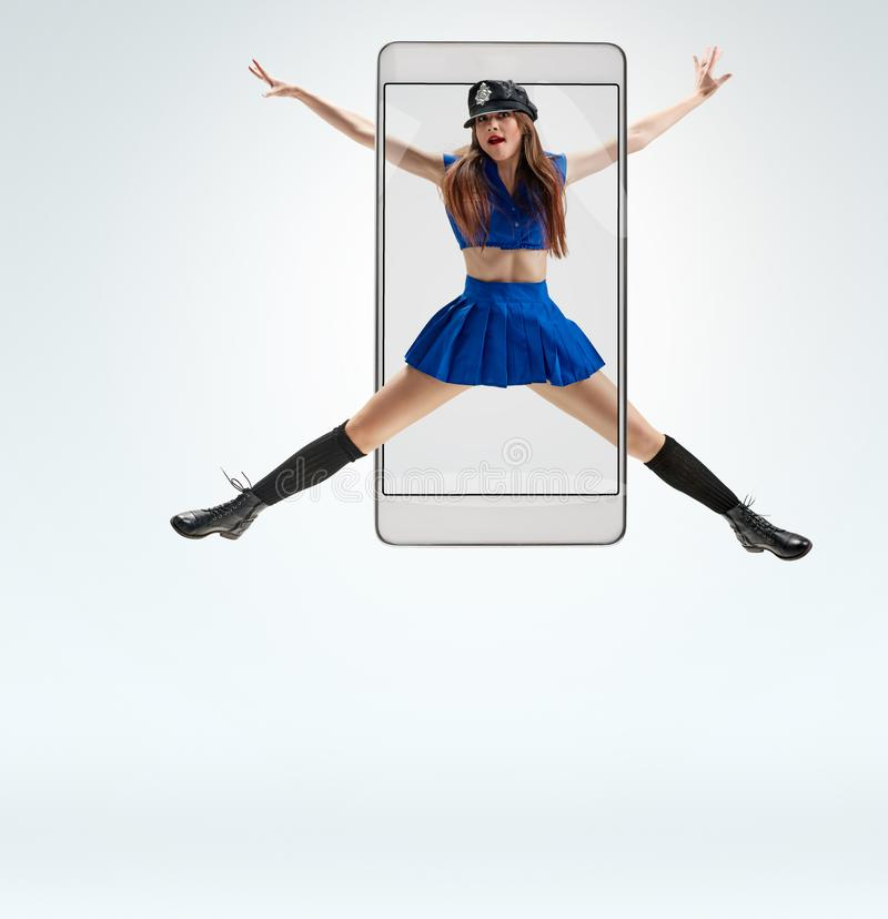 Female dancer jumping. Attractive positive woman in police uniform jumping while dancing, concept virtual reality of the smartphone. going out of the device stock photos