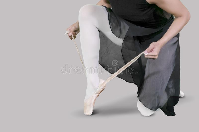 Female dancer ties up her ballet shoes stock photos
