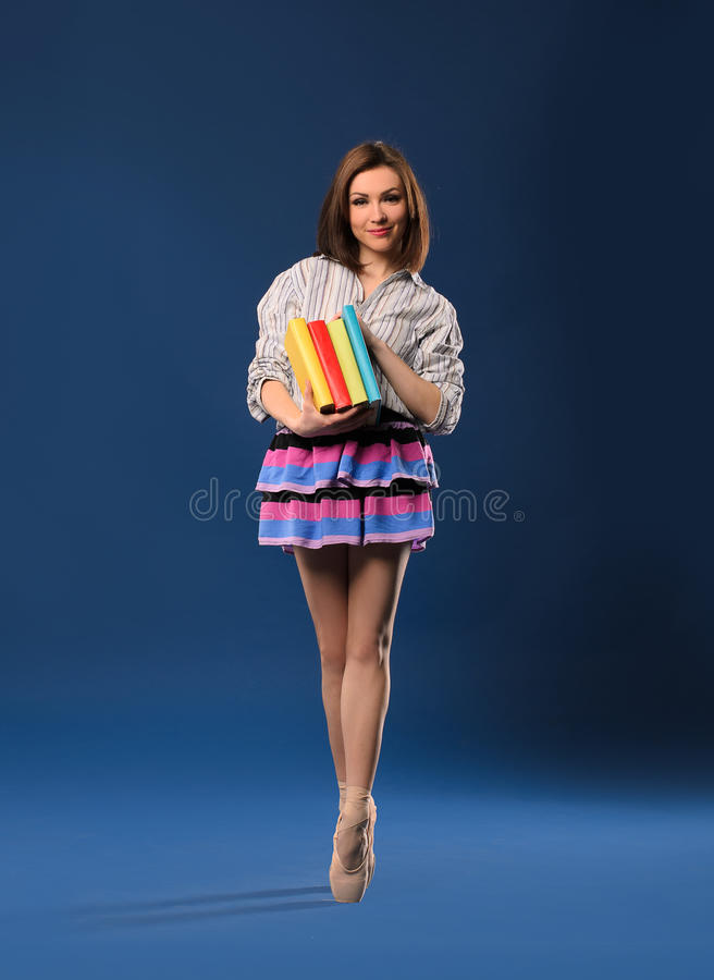 Female dancer on tiptoe with pile of books royalty free stock images